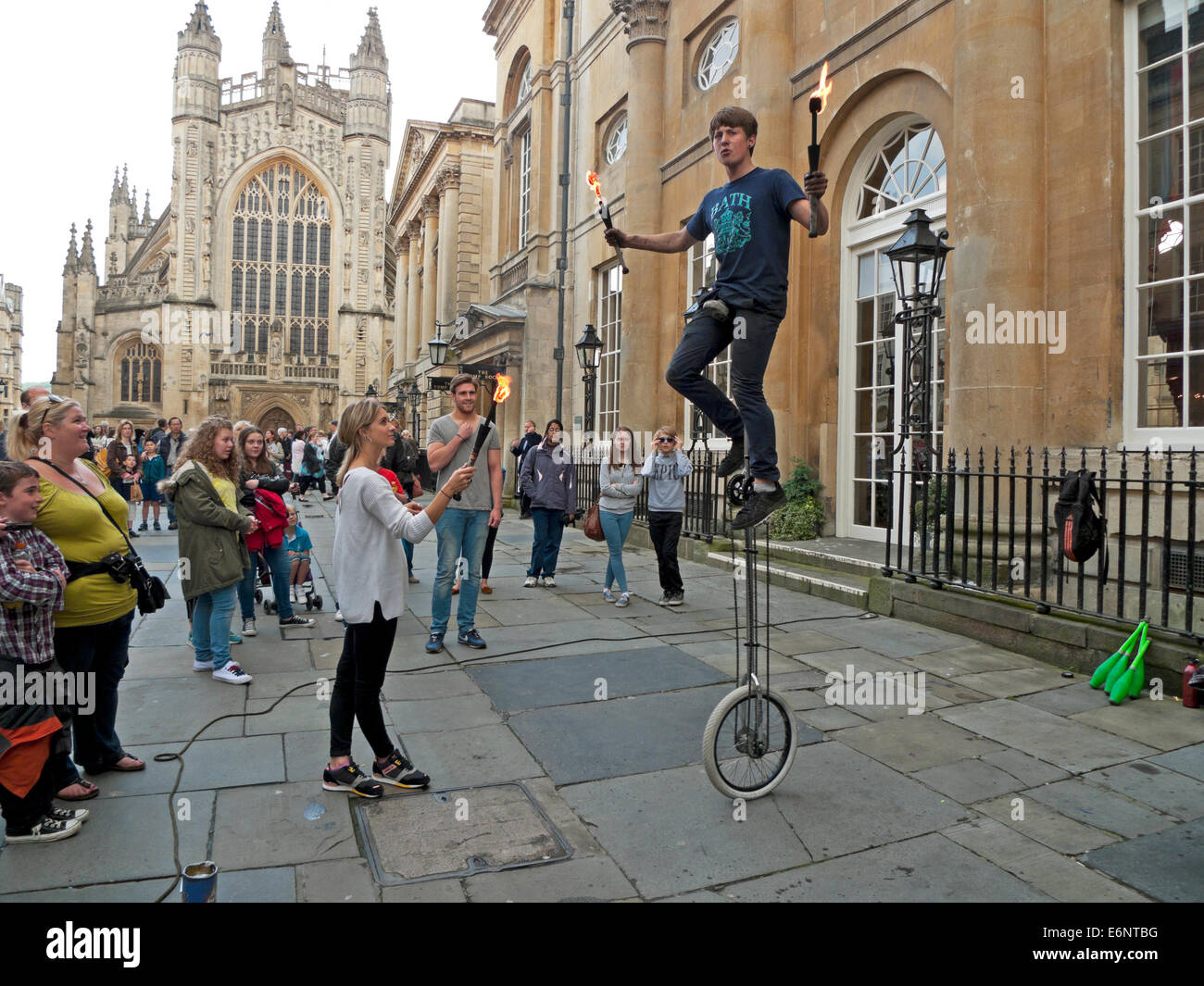 Street performer juggling with fire on a unicycle watched by tourists outside Bath Abbey Bath, England  KATHY DEWITT - Stock Image
