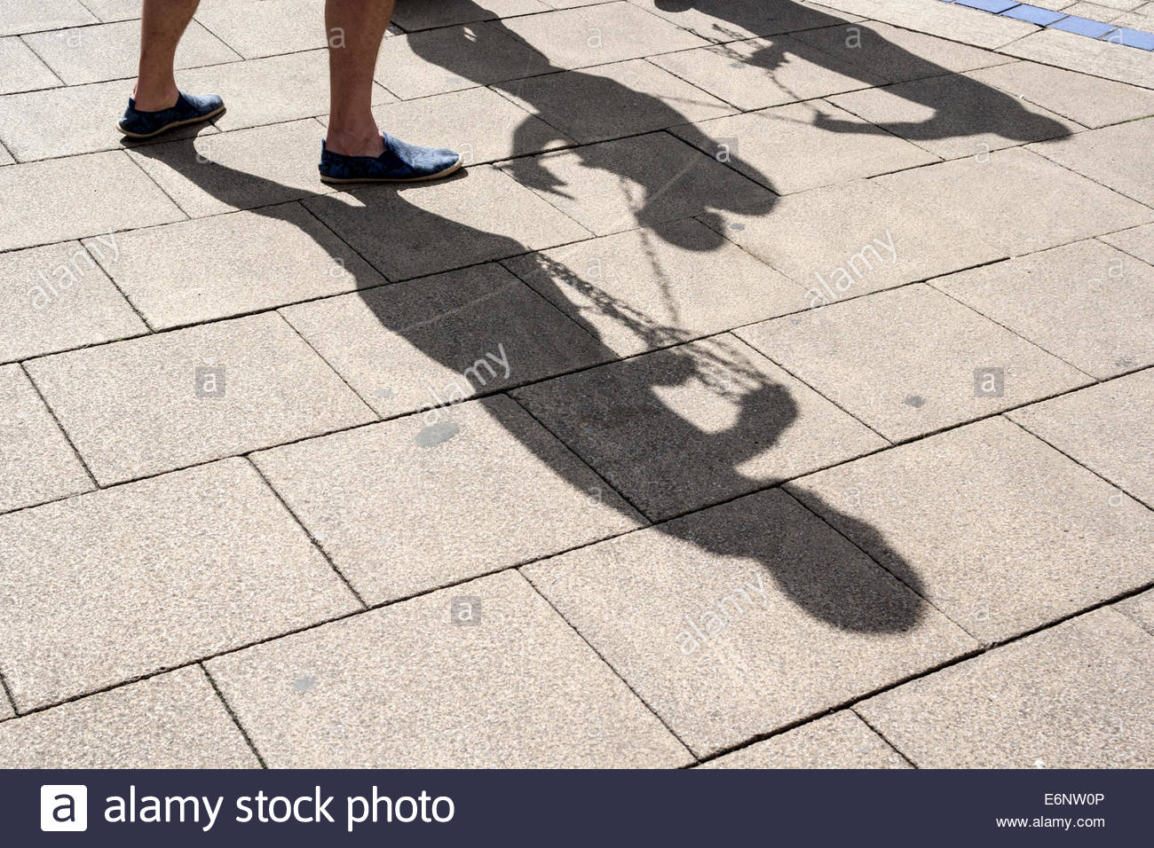 Shadows on a pavement.  Tied up in chains. - Stock Image