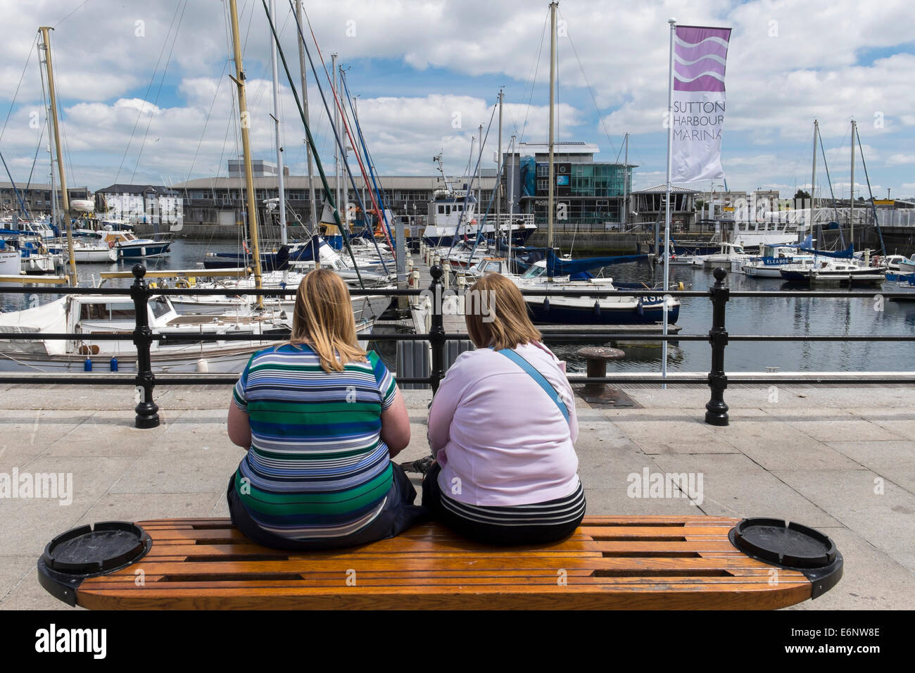 Two overweight women sitting on a bench on Plymouth Barbican, Plymouth, Devon, England, UK - Stock Image