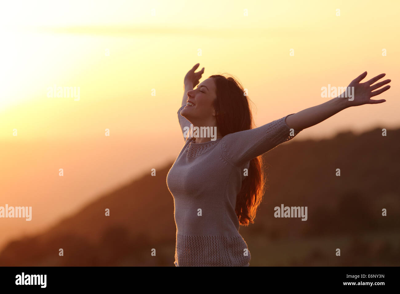 Backlit of  a woman at sunset breathing fresh air raising arms - Stock Image