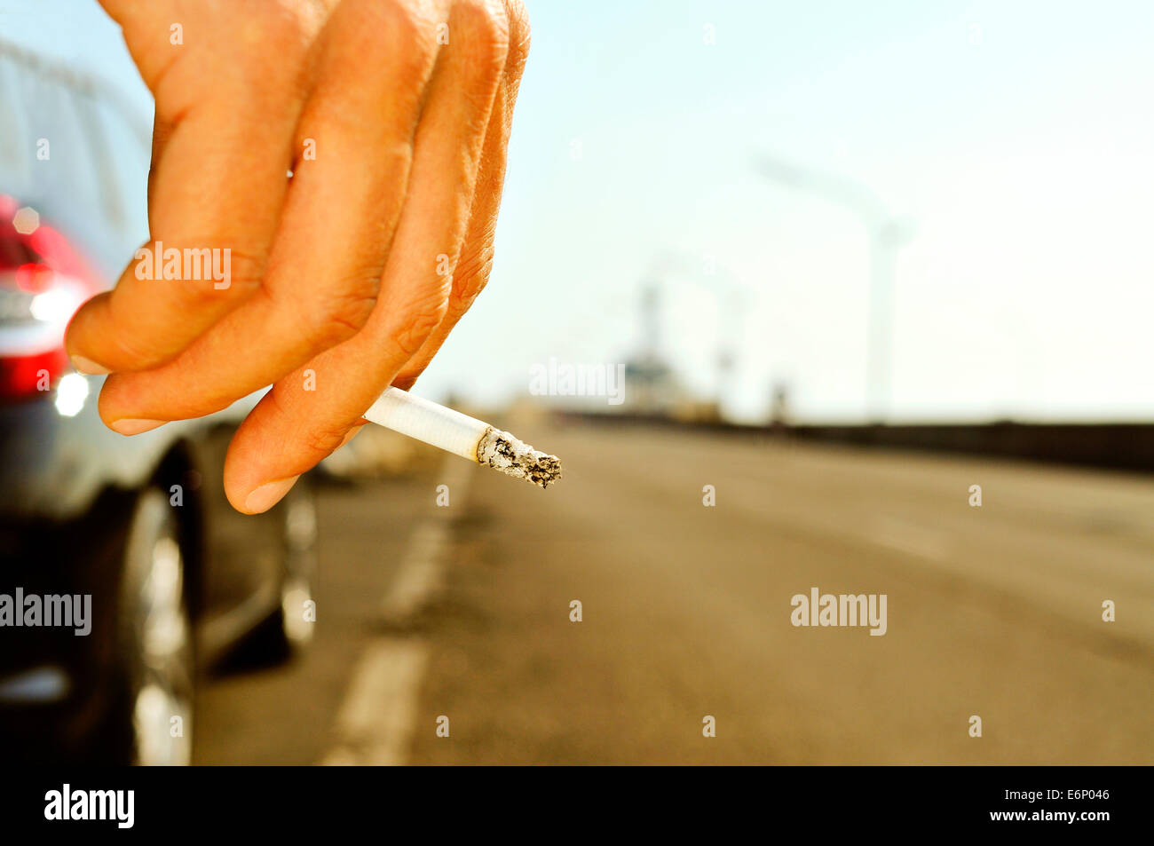 closeup of a man with a burning cigarette in his hand while is waiting besides a car parked next to a no traffic - Stock Image