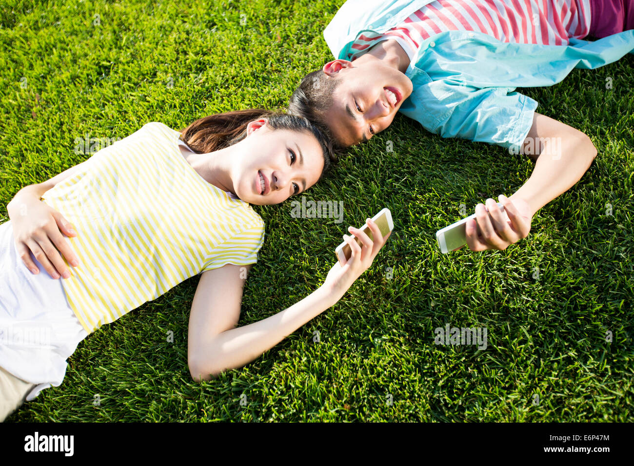 Cheerful young couple lying on grass with cell phones - Stock Image