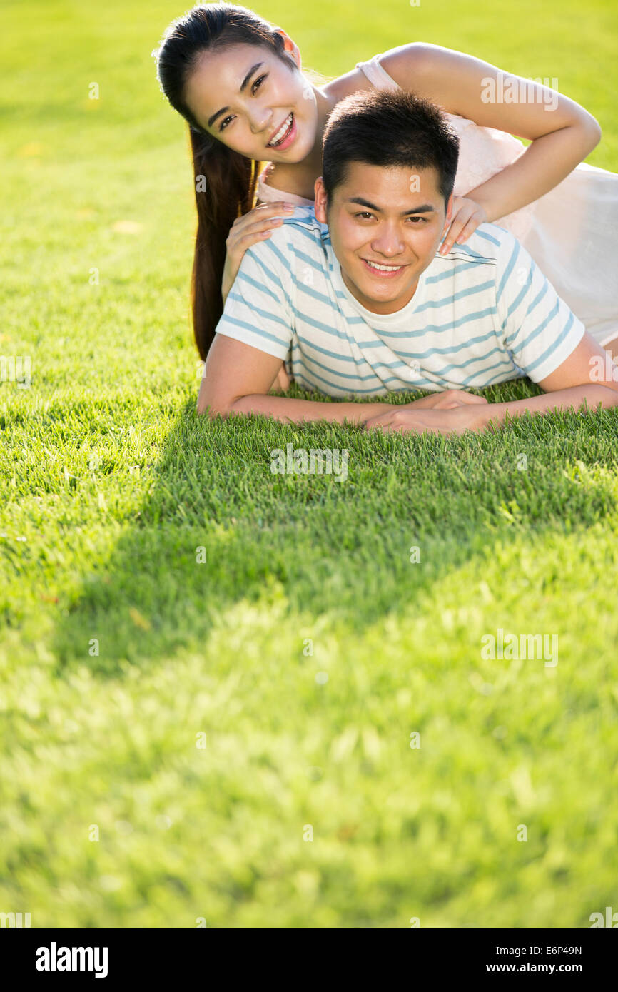 Cheerful young couple lying down on grass - Stock Image