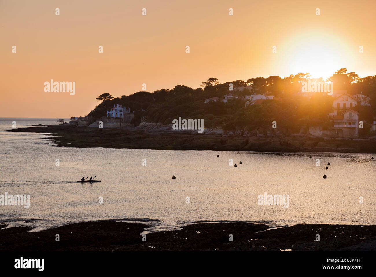 A two man canoe enters the bay at Conche de Saint Palais as the sun sets. - Stock Image