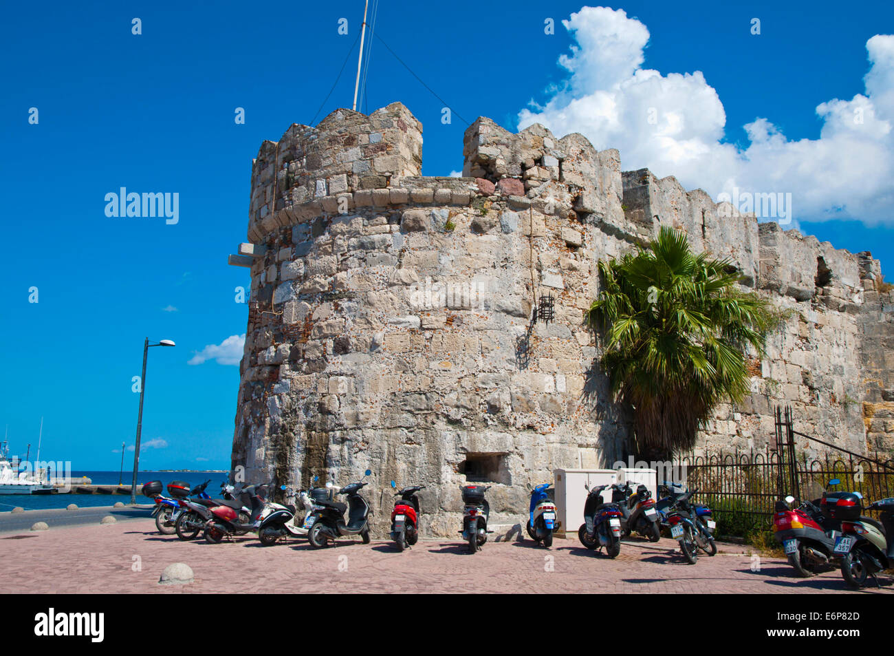 Scooters parked outside castle walls, the port, Kos town, Kos island, Dodecanese islands, South Aegean region, Greece, - Stock Image