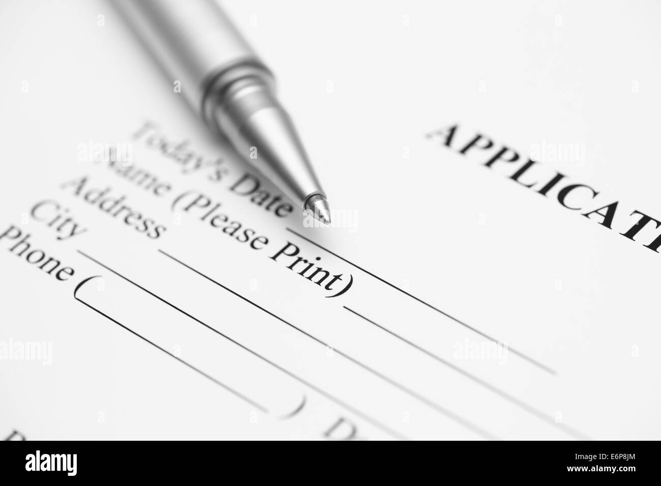 Application form and ballpoint pen. Focus on the end of ballpoint pen. Black and White. - Stock Image
