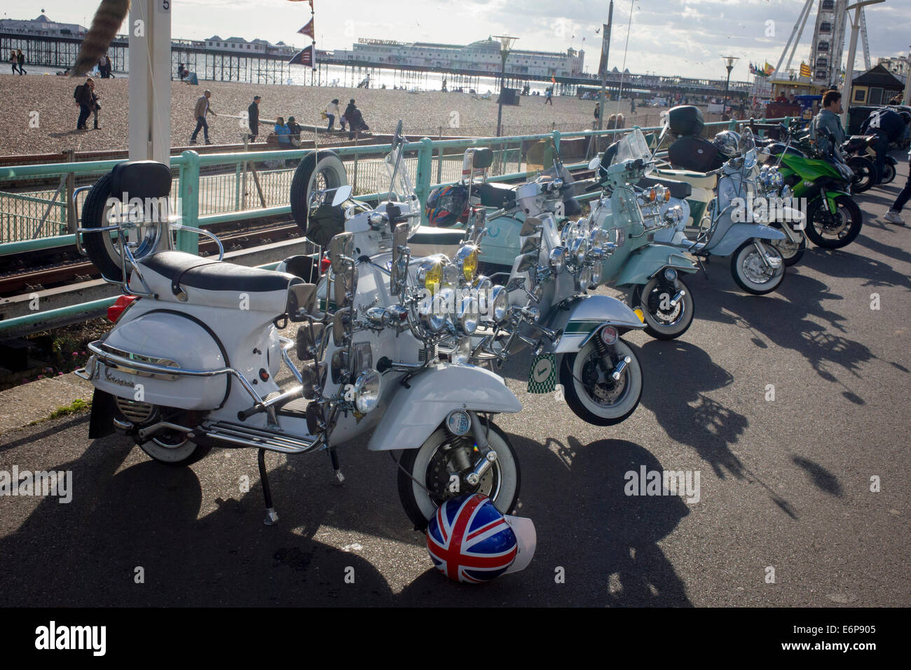 Vespa scooters on display on Brighton's seafront esplanade on Bank Holiday weekend. - Stock Image