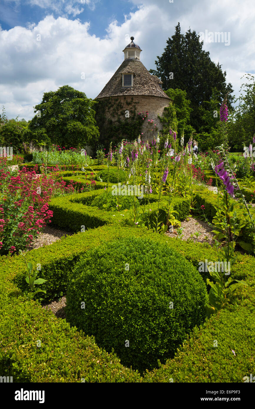 The box-hedged parterre with summer flowers and c.1685 dovecote in the walled garden of Rousham House, Oxfordshire, - Stock Image