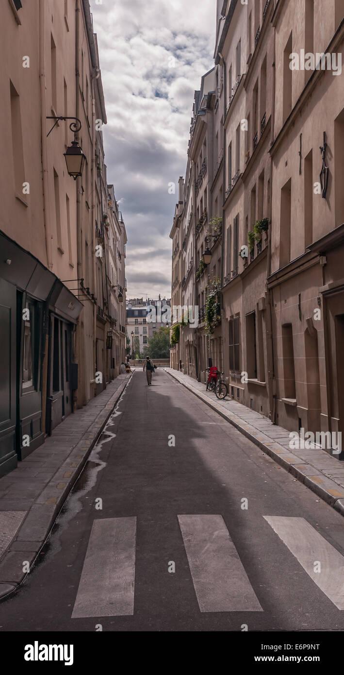 A man walking down a narrow street on Ile St Louis Paris France. - Stock Image