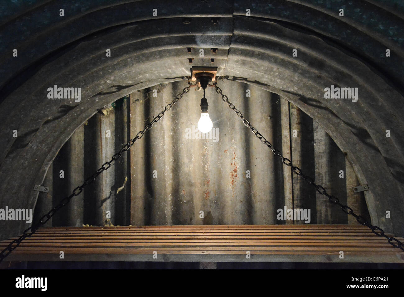 Bare lightbulb over a wooden bunk inside a World War II Anderson air raid shelter - Stock Image