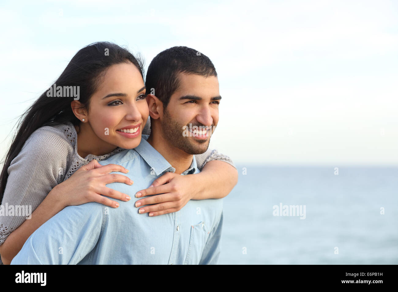 Arab couple flirting piggyback in love on the beach with the sea in the background - Stock Image