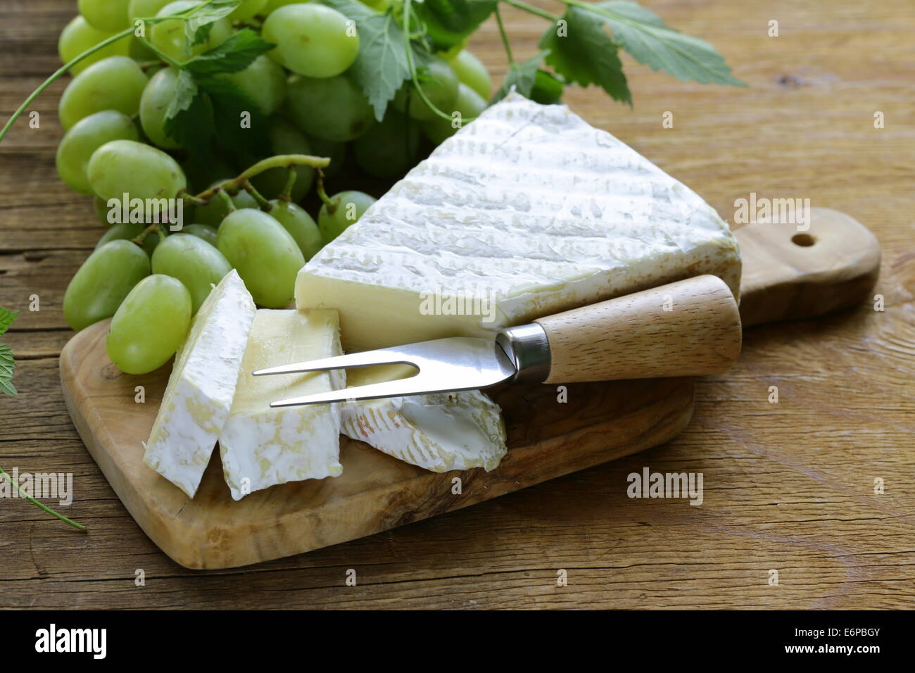Soft brie cheese with sweet grapes on a wooden board - Stock Image