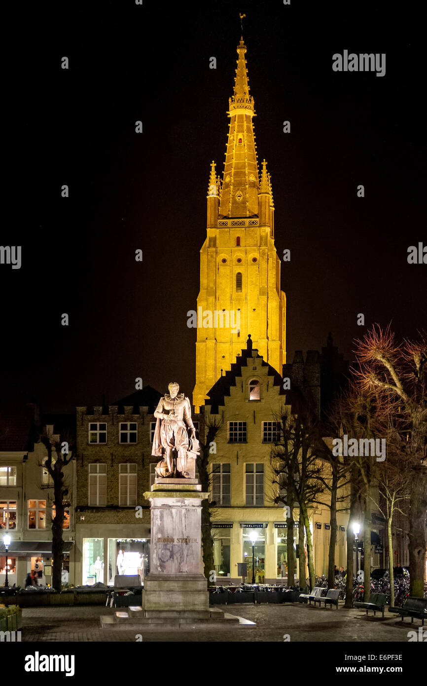Night scene with the statue of mathematician Simon Stevin and Bruges' Church of our Lady in the background - Stock Image