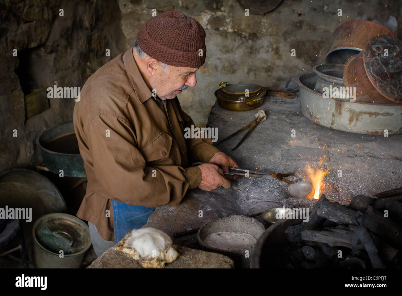 An old traditional coppersmith at work in his workplace, in the city of Mardin, Southeastern Anatolia, Turkey. Model - Stock Image