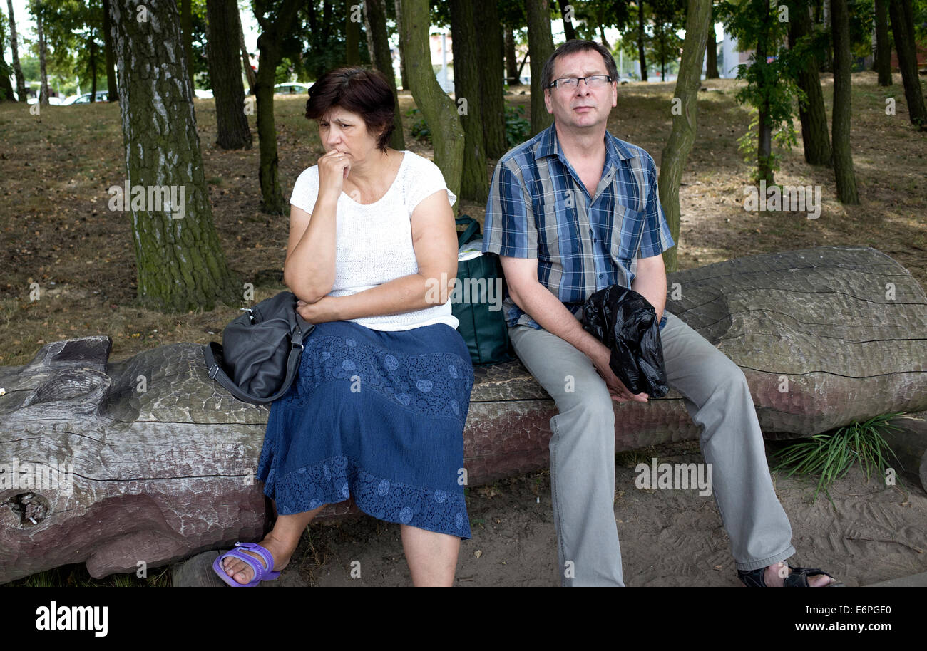 Polish couple appearing apprehensive at city park. Rawa Mazowiecka Poland - Stock Image