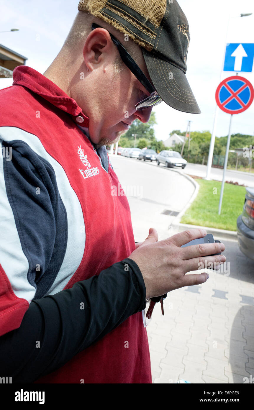 Man age 39 totally absorbed while texting on his mobile cell phone outside. Rawa Mazowiecka Poland - Stock Image