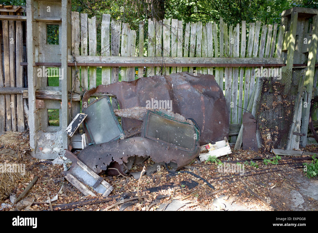 Remnants of an automobile leaning against an old slatted wooden fence in a back yard Rzeczyca Poland - Stock Image