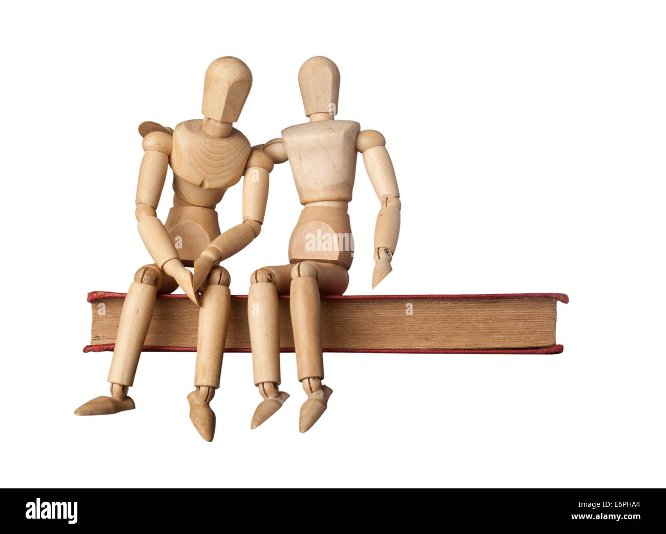 Consolation of a friend depicted by two figurines on a book isolated on white background - Stock Image