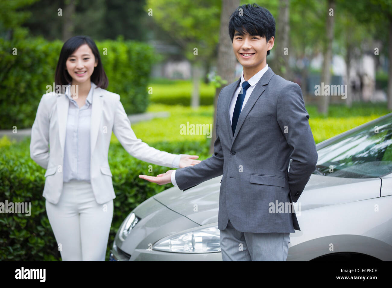 Young business person doing welcome gesture Stock Photo