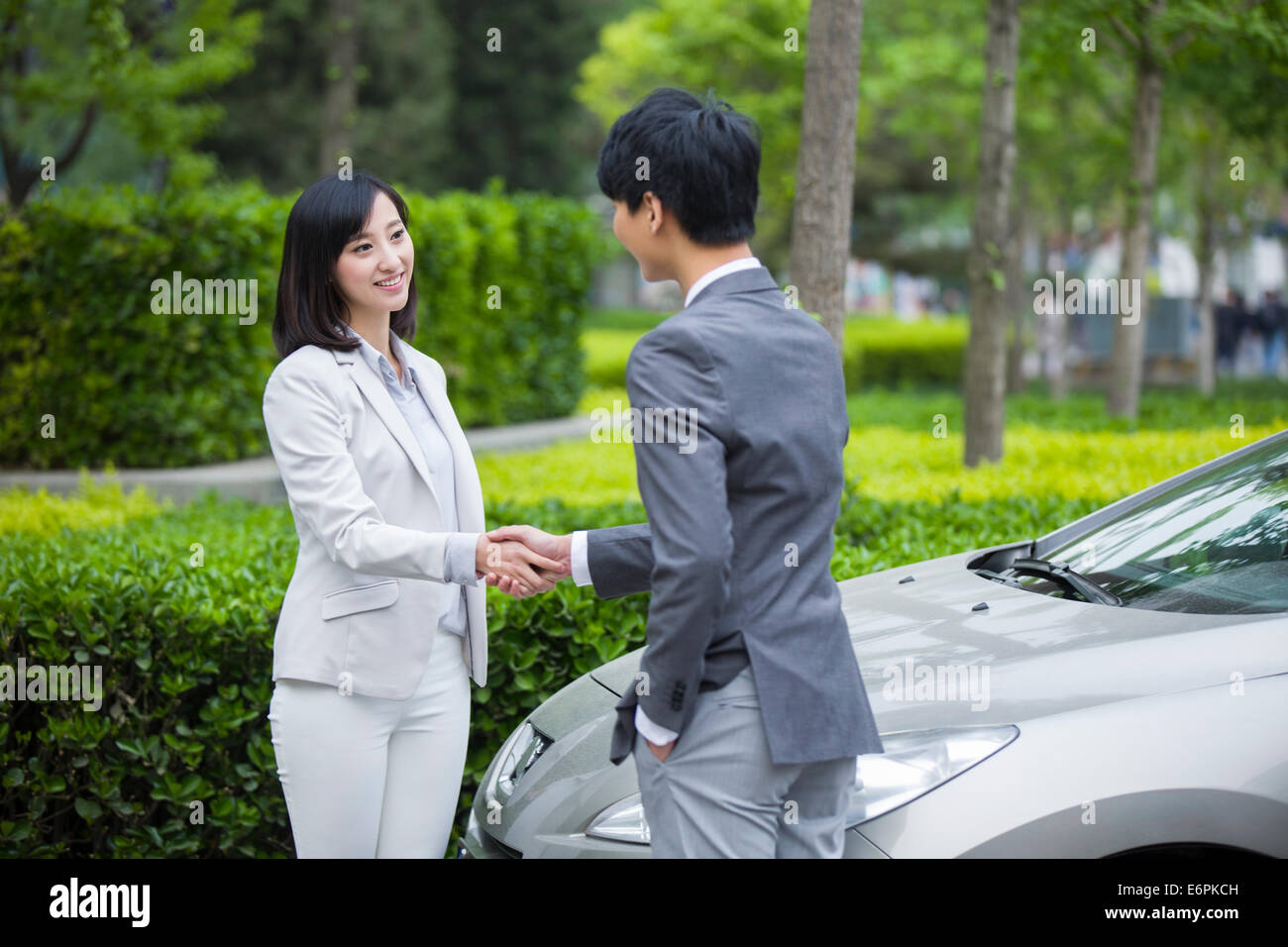 Young business person shaking hands - Stock Image