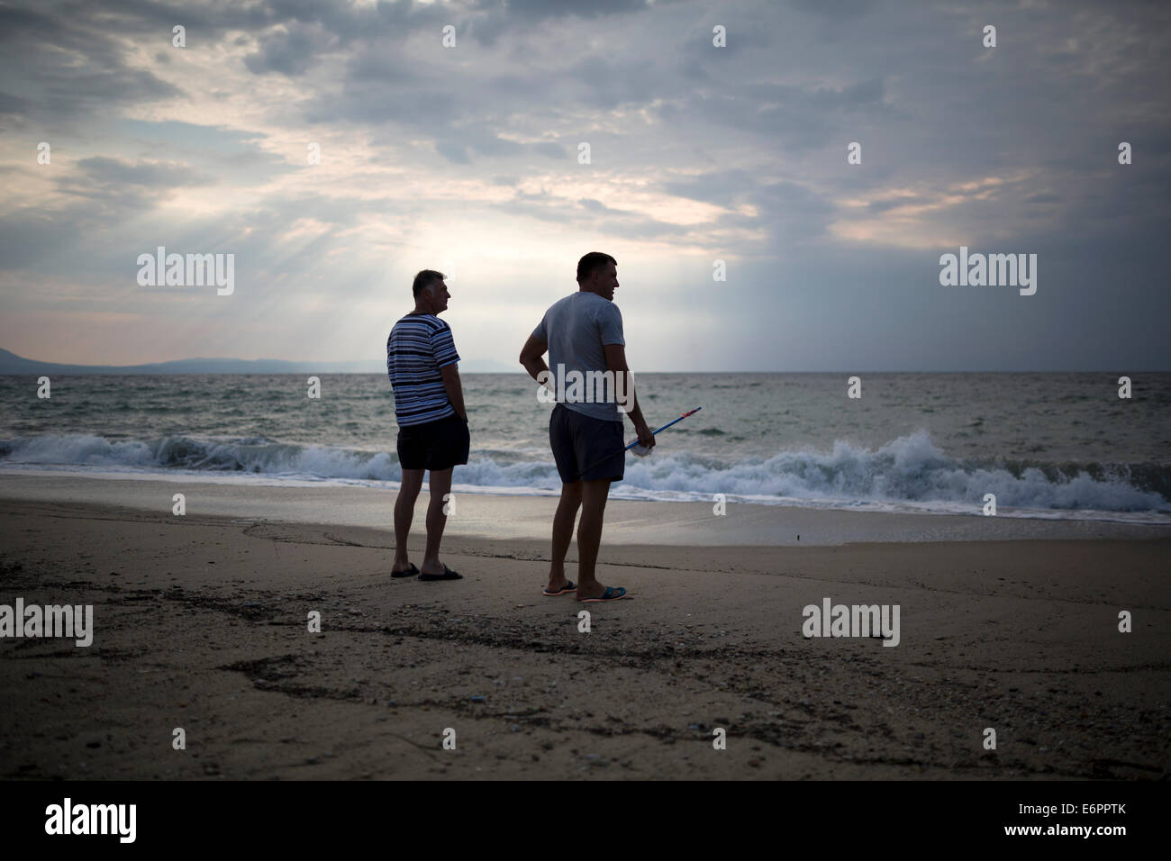 Thessaloniki, Greece. 29th August, 2014. Two men gaze to sea during a morning walk on the beach. Morning stroll - Stock Image