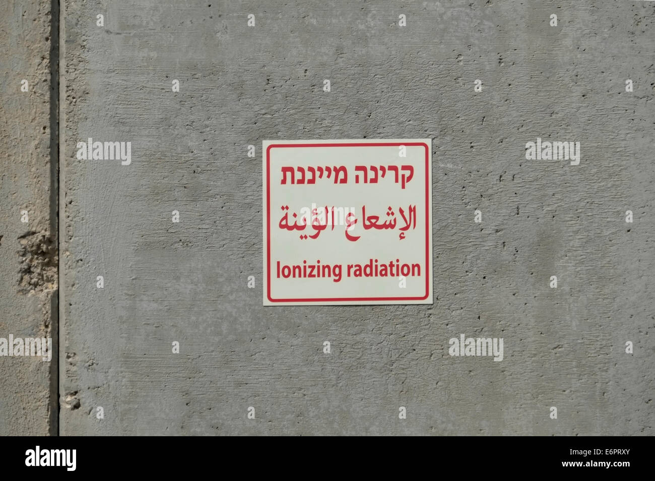 Ionizing radiation sign in Hebrew Arabic and English attached to security wall in the cargo inspection area in Kerem - Stock Image
