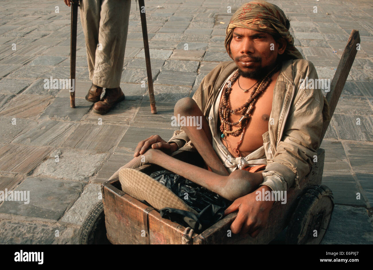Beggar suffering from poliomyelitis on a cart. In the background, another beggar with crutches ( Nepal) - Stock Image