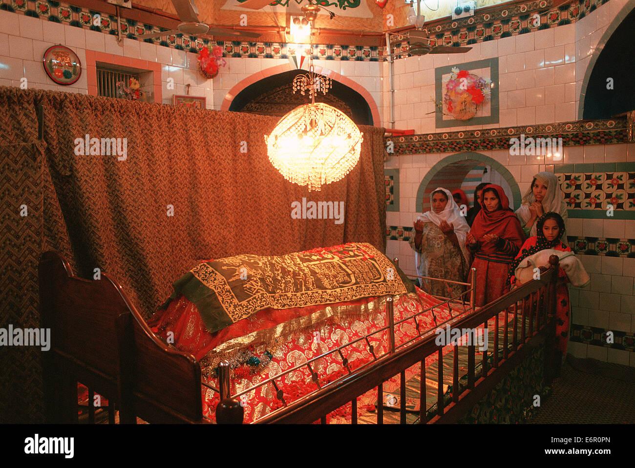 Muslim women praying on the tomb of a respected muslim man ( Pakistan) - Stock Image