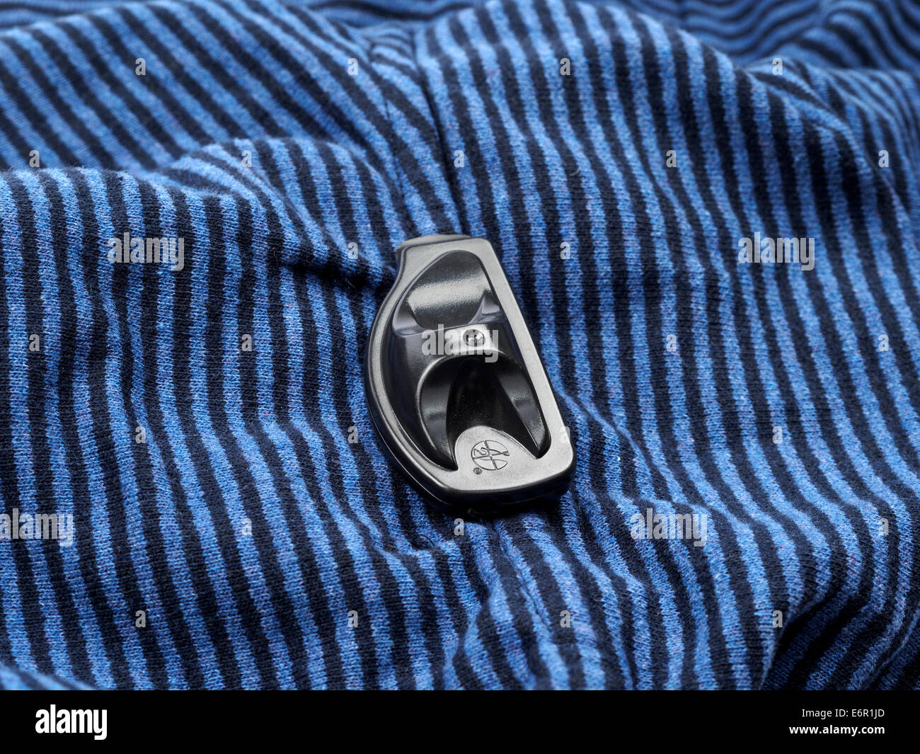 Close up of store security tag on clothing used to prevent theft - Stock Image