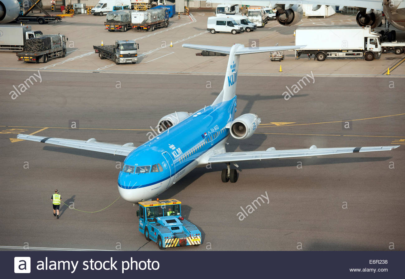 London UK London Heathrow Airport (LHR) KLM Fokker being pushed away from the terminal by a tug. - Stock Image