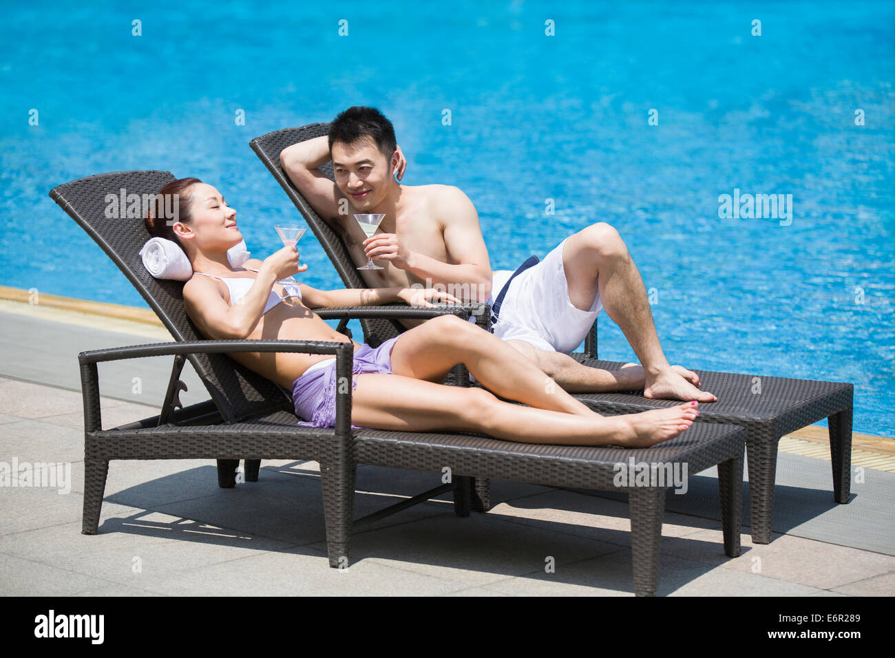 Young couple sunbathing at the poolside - Stock Image