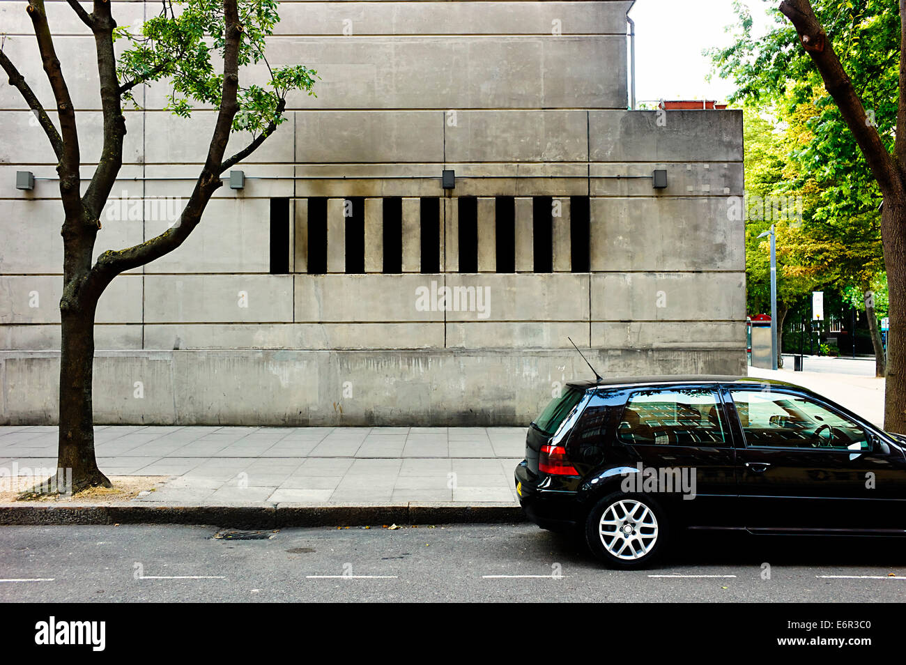 Concrete building window and parked car - Stock Image