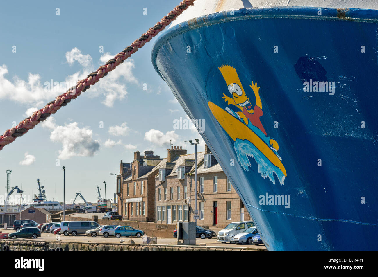 PETERHEAD HARBOUR ABERDEENSHIRE BART SIMPSON AND SURFBOARD ON THE PROW OF A FISHERIES TRAWLER - Stock Image