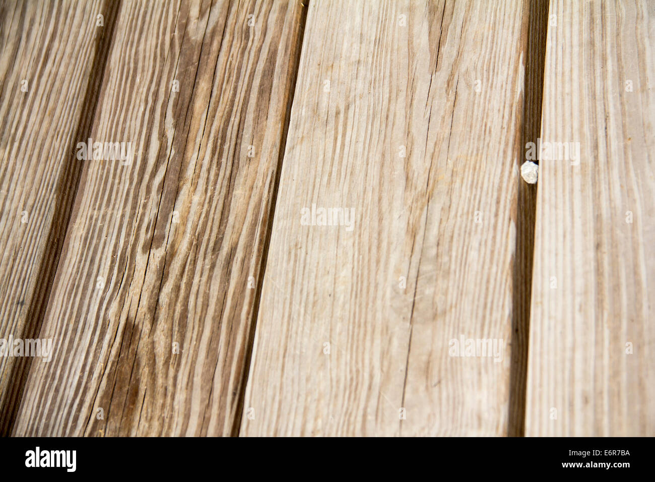 Wood Grain Background with Pebble Wedged in Between - Stock Image