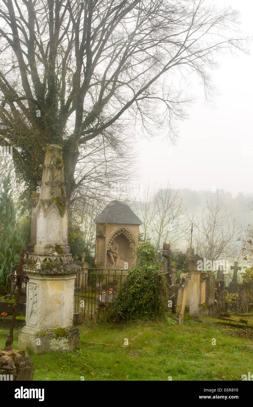Mist hanging over a medieval graveyard in France - Stock Image