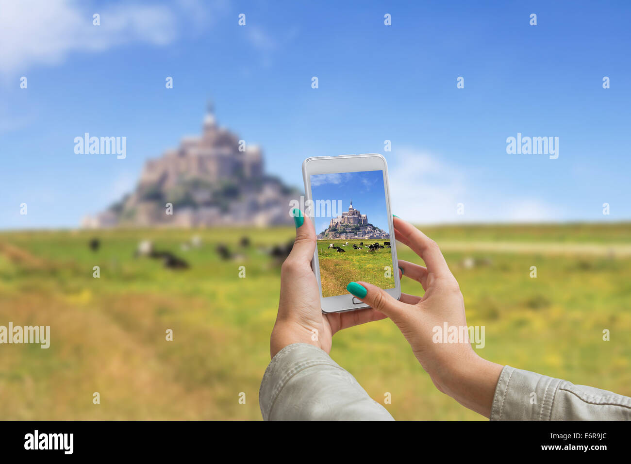 Girl taking pictures on a cellphone, Le Mont Saint Michel Abbey, Normandy / Brittany, France - Stock Image
