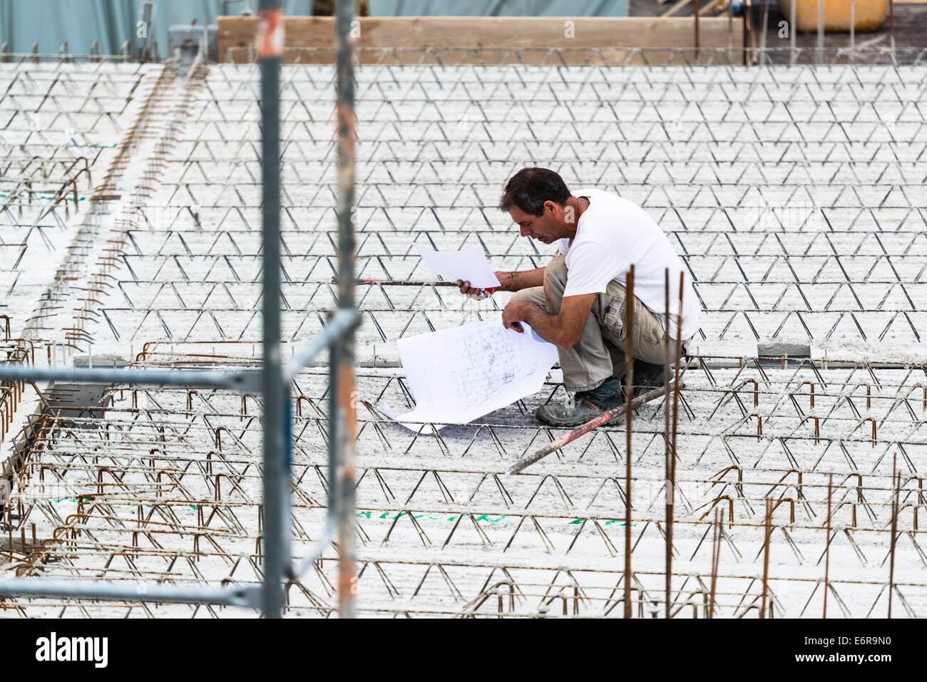 Eengineer checking a blueprint on construction site - Stock Image