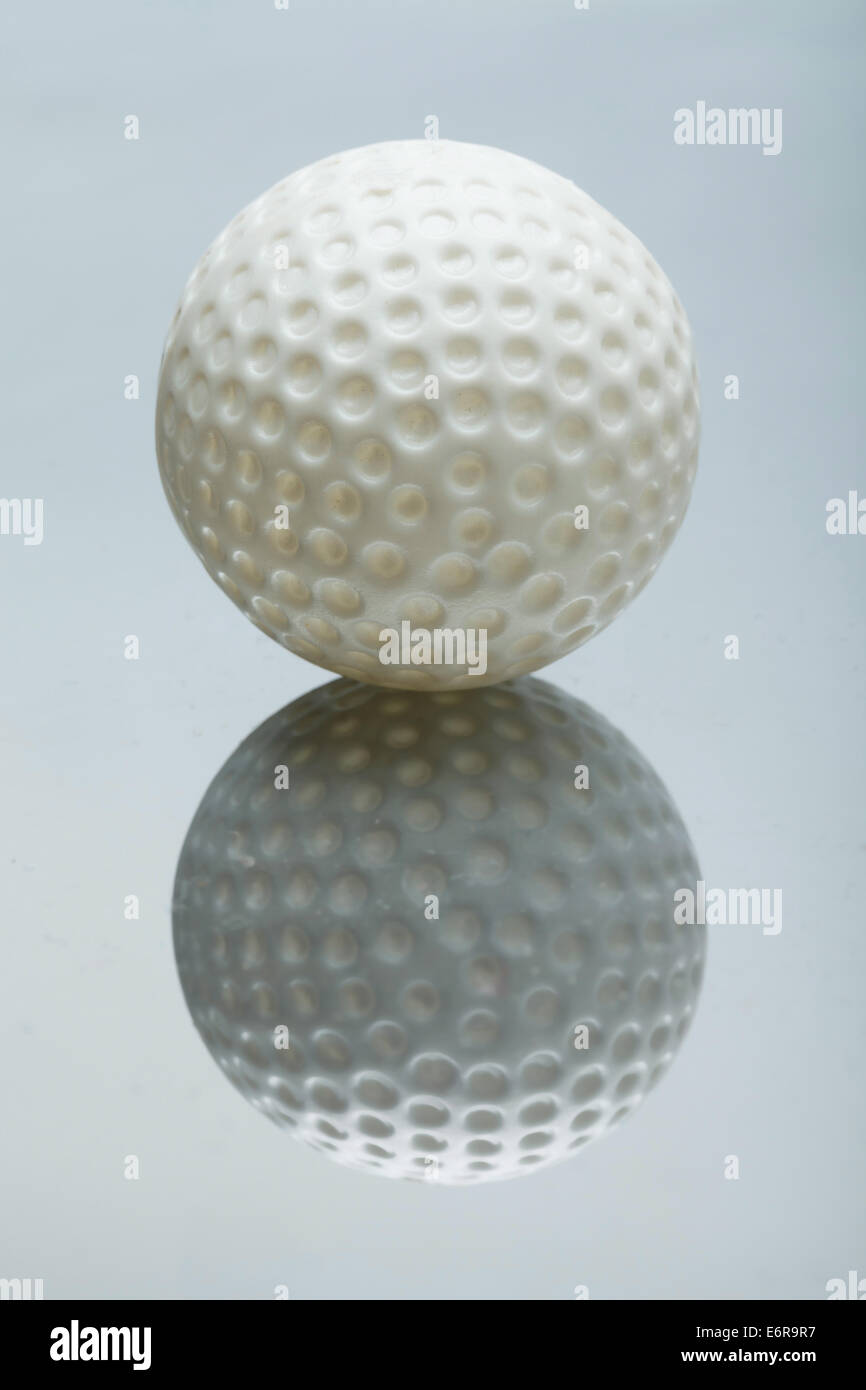 white Mini Golf ball on mirrored background - Stock Image