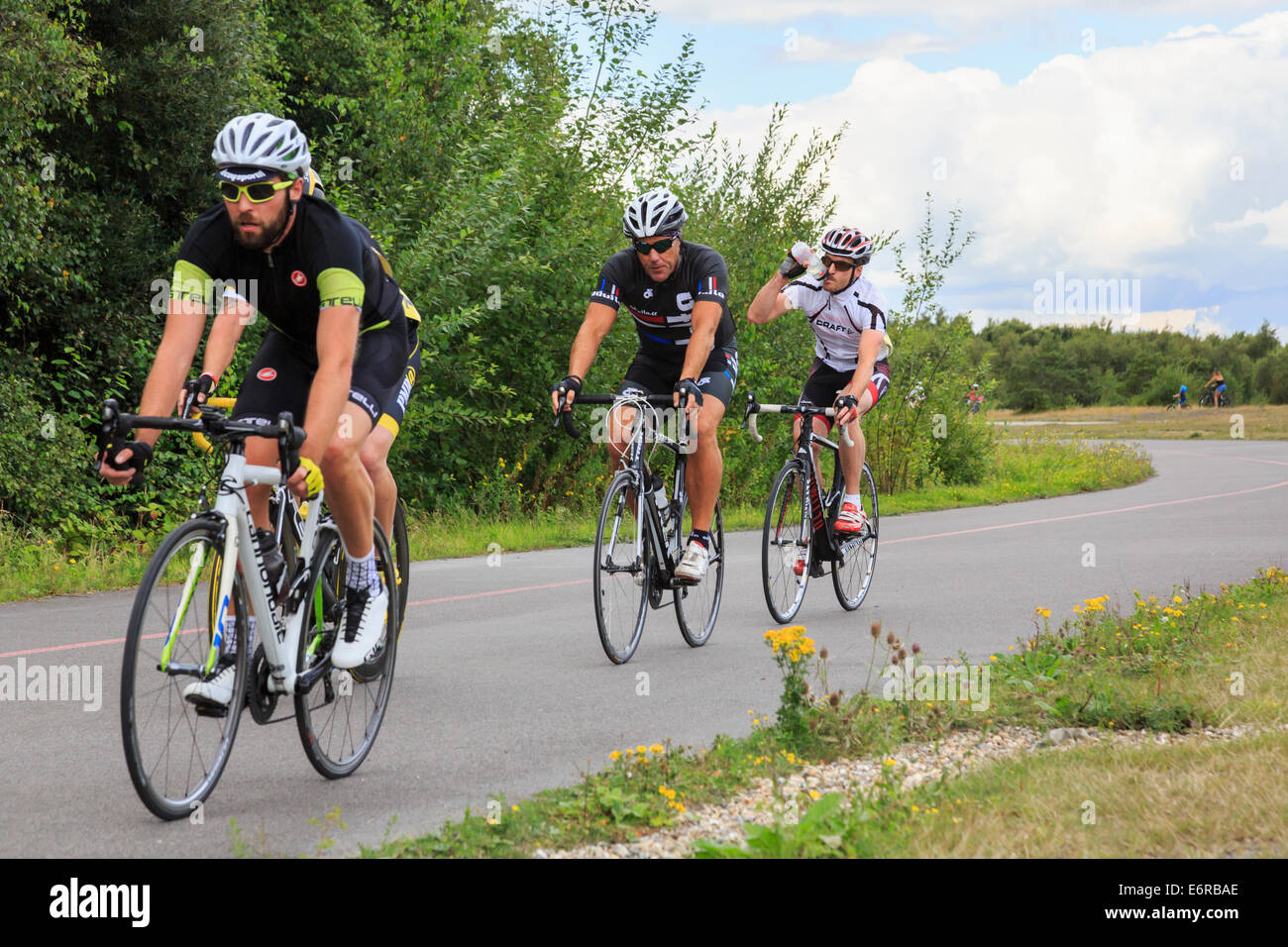Cyclist drinking water whilst racing in a local bike race organised by British Cycling at Fowlmead Country Park - Stock Image