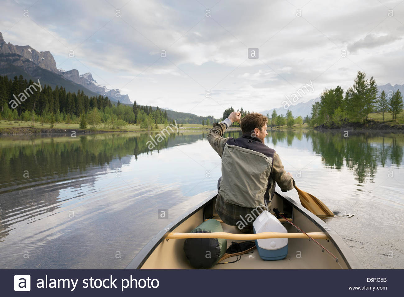 Man rowing canoe in still lake - Stock Image