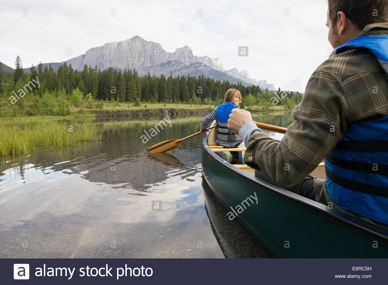 Father and son rowing canoe in still lake - Stock Image