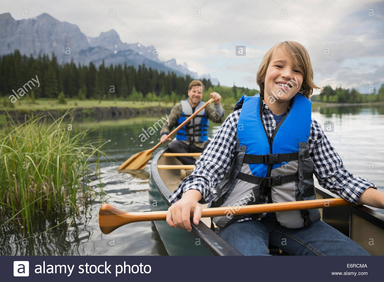 Father and son rowing canoe in lake - Stock Image