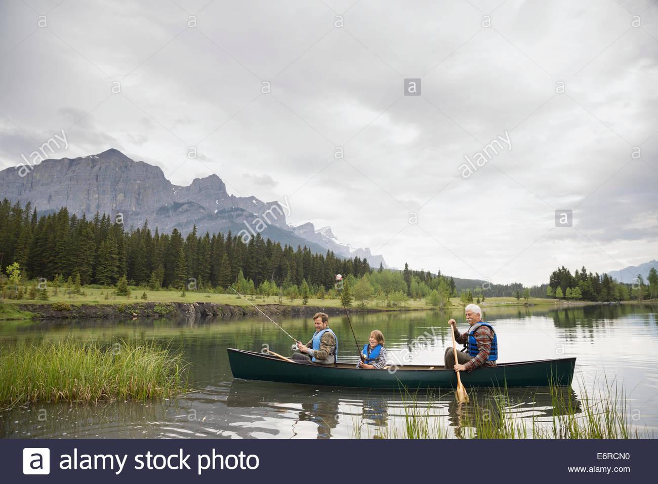 Three generations of men fishing in lake - Stock Image