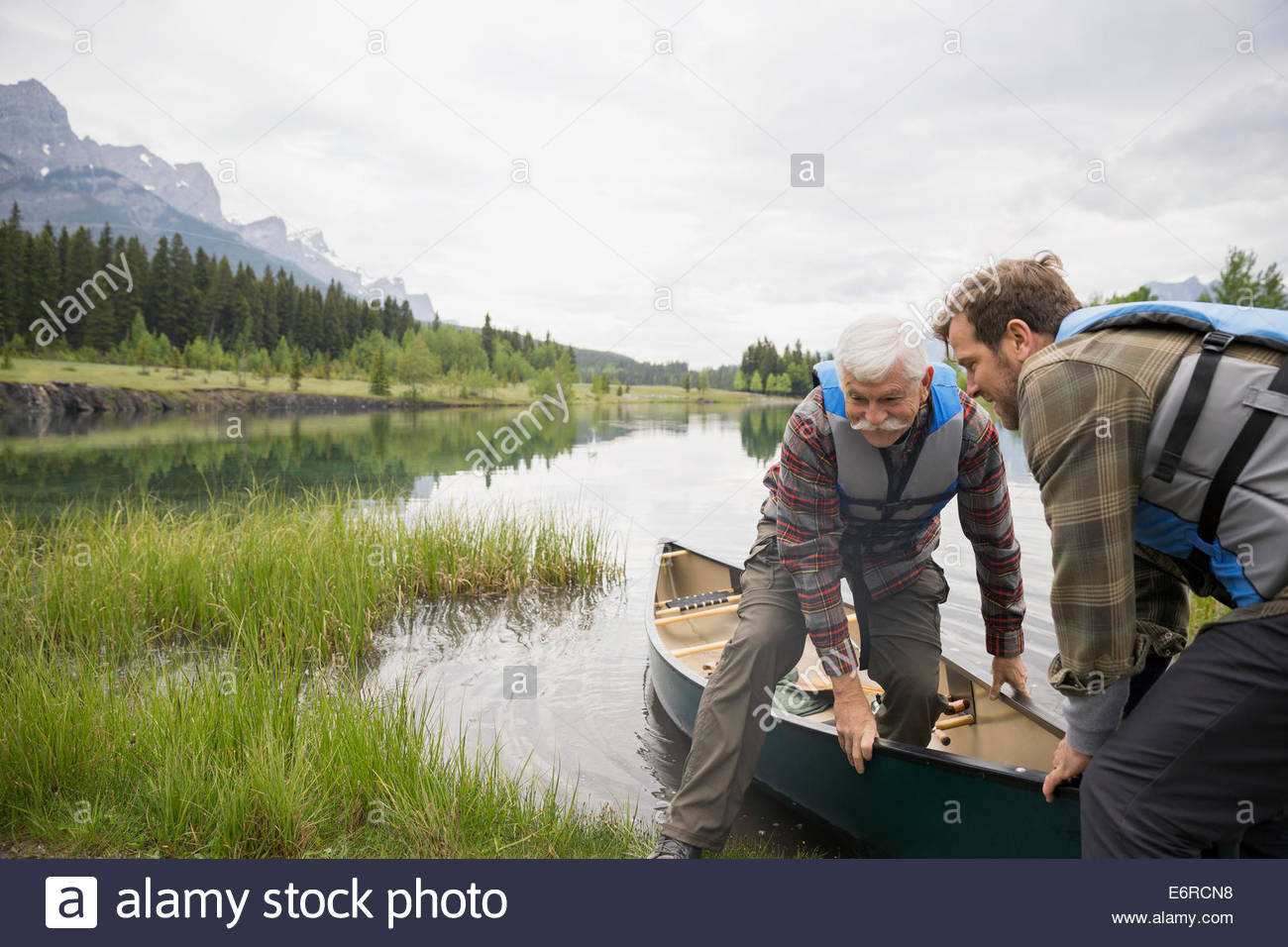 Son helping father out of canoe - Stock Image