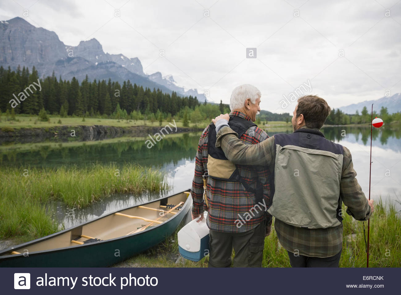 Father and son overlooking still lake - Stock Image