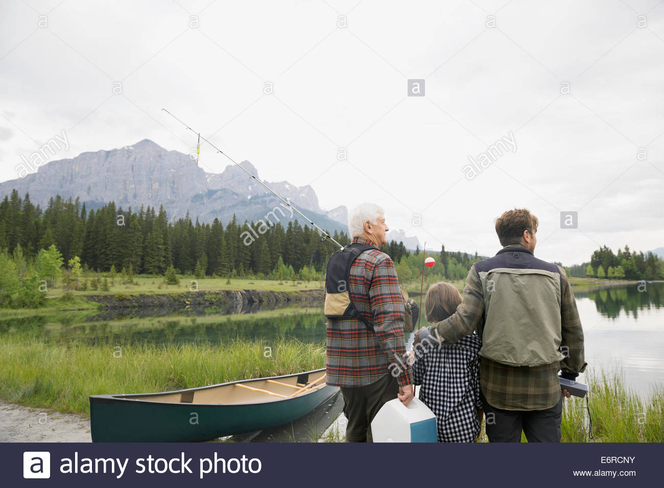 Three generations of men overlooking still lake - Stock Image
