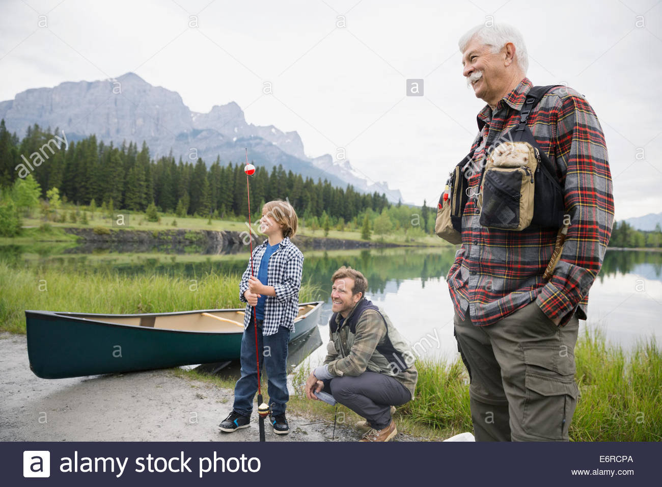 Three generations of men by still lake - Stock Image