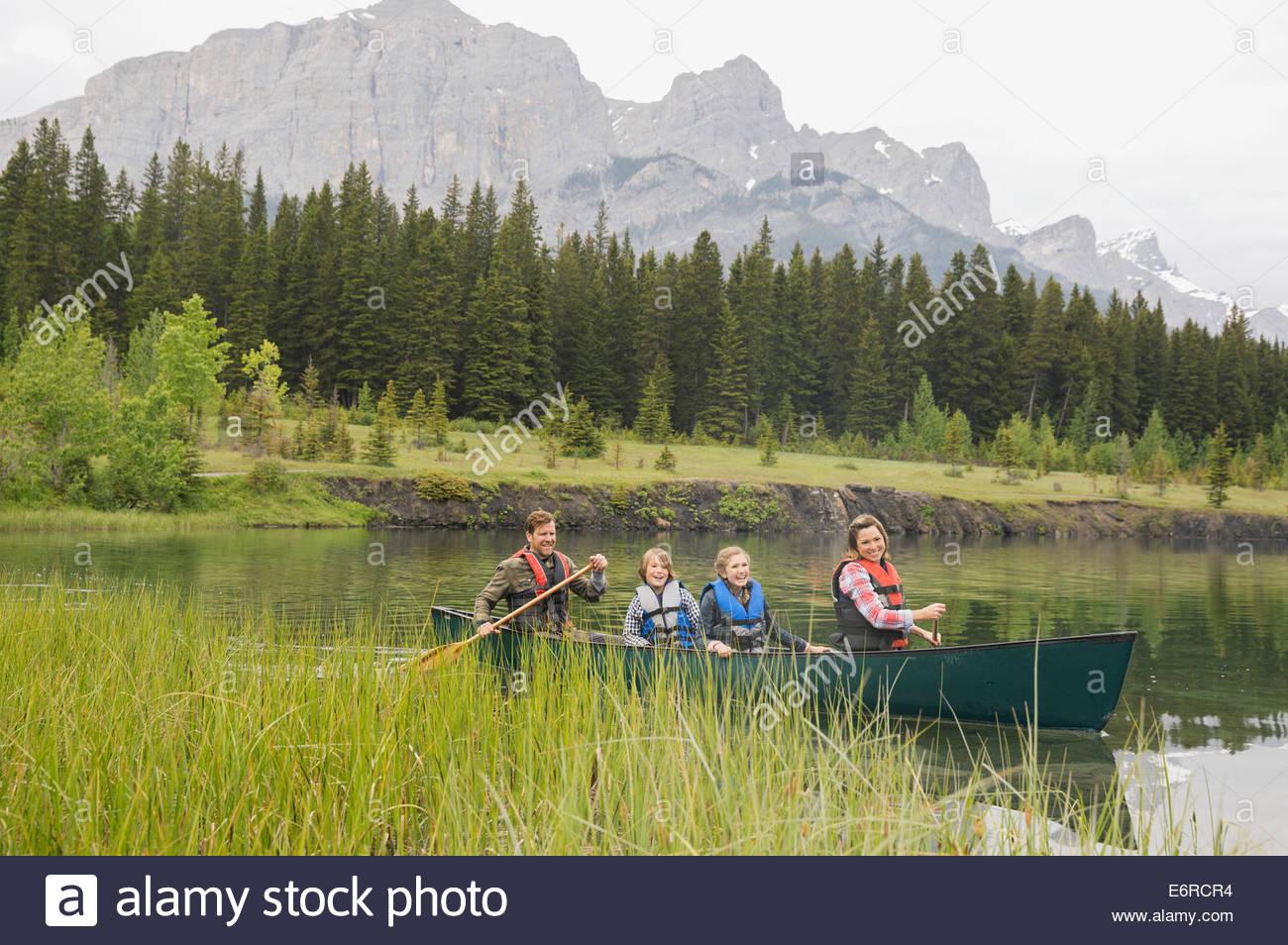 Family rowing canoe in still lake - Stock Image