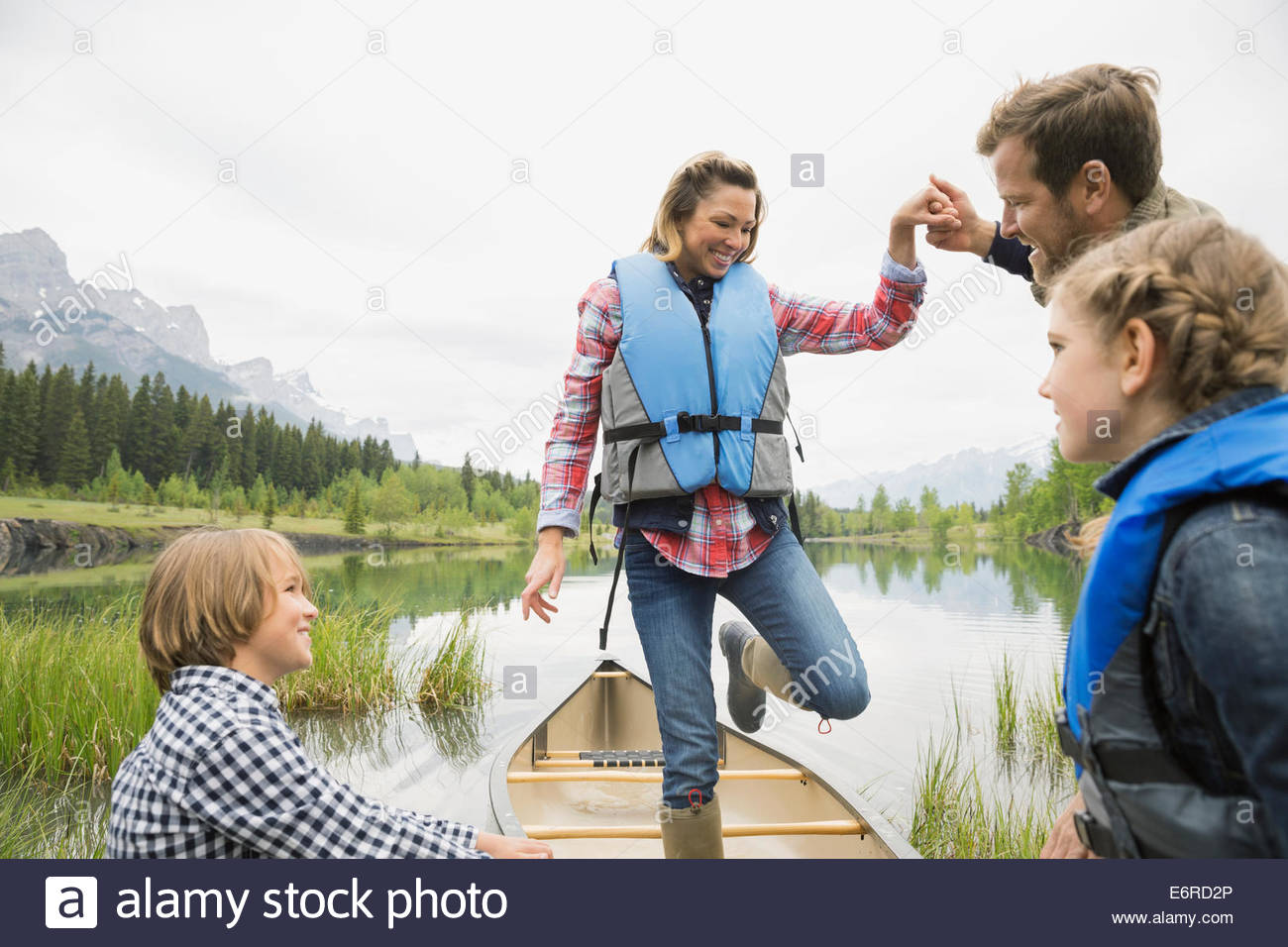 Husband helping wife from canoe in still lake - Stock Image