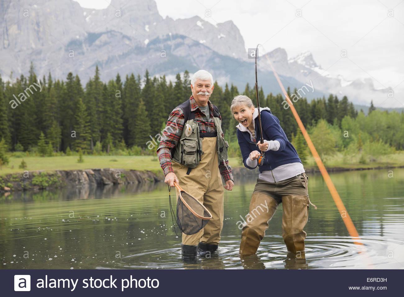 Older couple fishing in still lake - Stock Image